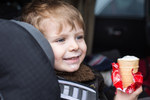Adorable toddler boy with blue eyes in safety car seat eating sweet ice cream