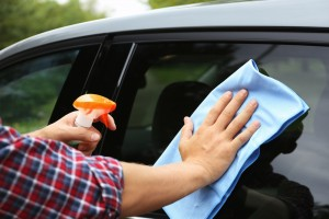 Man washing car window with rag outdoors, closeup